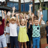 a woman with a group of children raising their hands